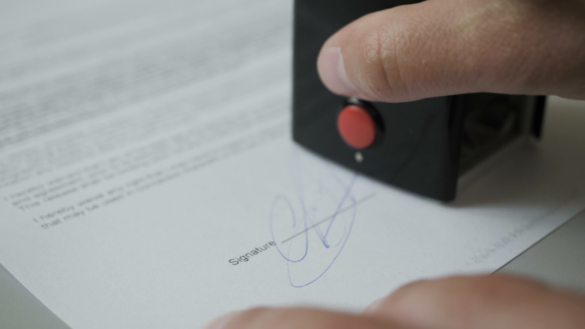 Notary public in office stamping document. Businessman stamping document table, director approving contract, paperwork. Man is approve documents by signing and stamping papers. Closeup. UHD 4K.
