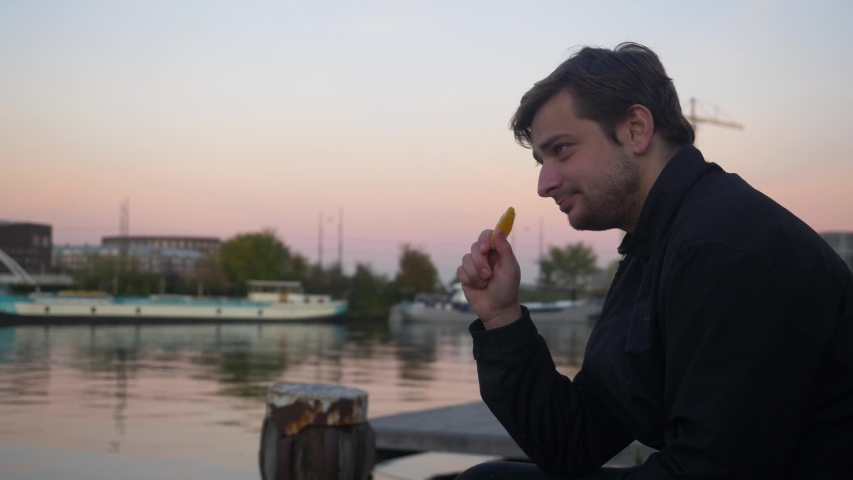 Wide shot of a young man snacking on an orange slice and smiling on a water pier during sunset | Shutterstock HD Video #1029980252
