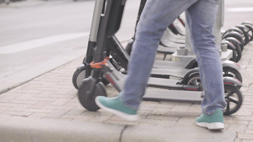 A man parks his electric scooter next to a row of other shared scooters   Shutterstock HD Video #1029992240