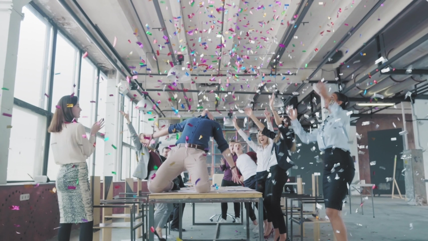 Manager start to dance on the table, sings into a megaphone, accelerates and slide on lap. Colleagues blow up flappers with confetti. Employees celebrate success. Corporate party business team #1029993728