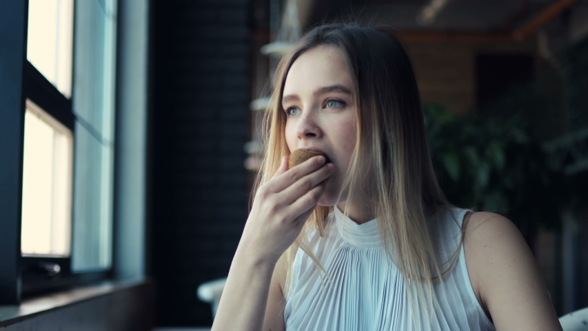 Portrait of Beautiful young woman eating kiwi fruit on lunch break in hallroom living healthy lifestyle. Fashion bueaty girl. delight of delicious food #1030003952