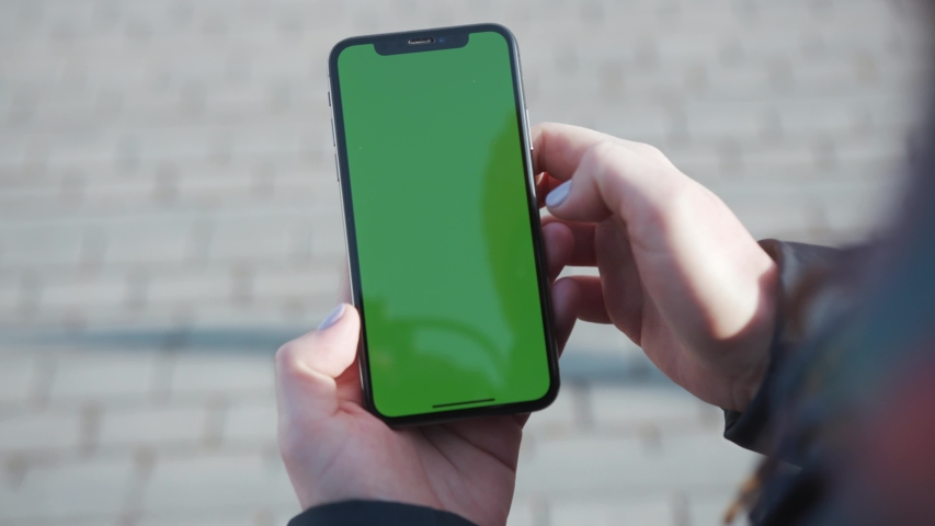 NEW YORK - 5 April 2018: Close up woman hands holding smart phone with green screen on the city street background pavement sunset message busy key city finger text building call evening slow motion | Shutterstock HD Video #1030007945