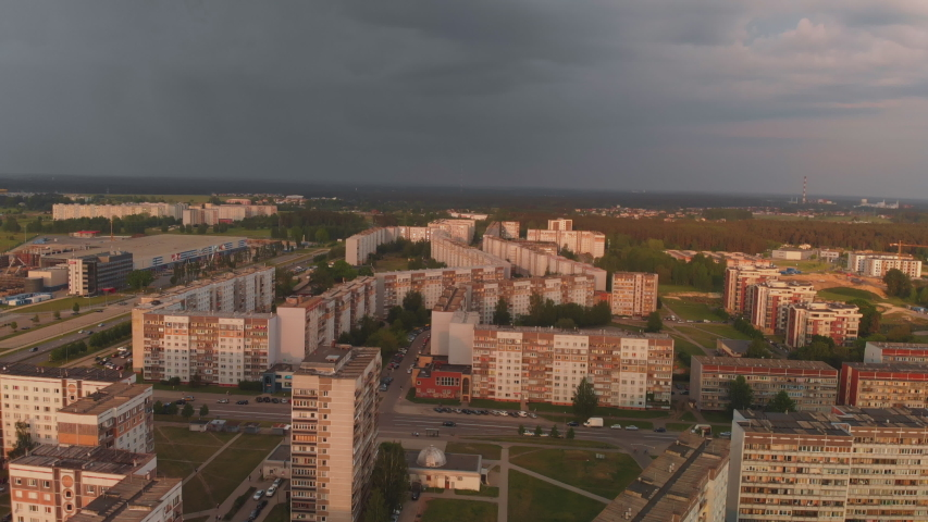 Aerial top view of storm coming arriving at a district of Soviet design - Sunset in european capital Riga, Latvia - Urban Landscape scenery with professional smooth movement and camera angles