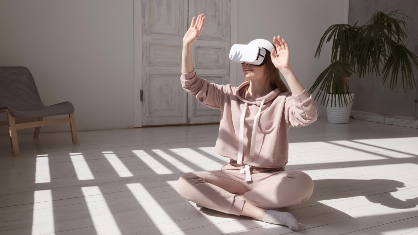 Beautiful young girl wearing virtual reality headset. Augmented Reality. Happy cute woman touch something using modern 3D vr glasses indoors. Woman playing using VR glasses on a sunny day. Shot on 4K | Shutterstock HD Video #1030030382