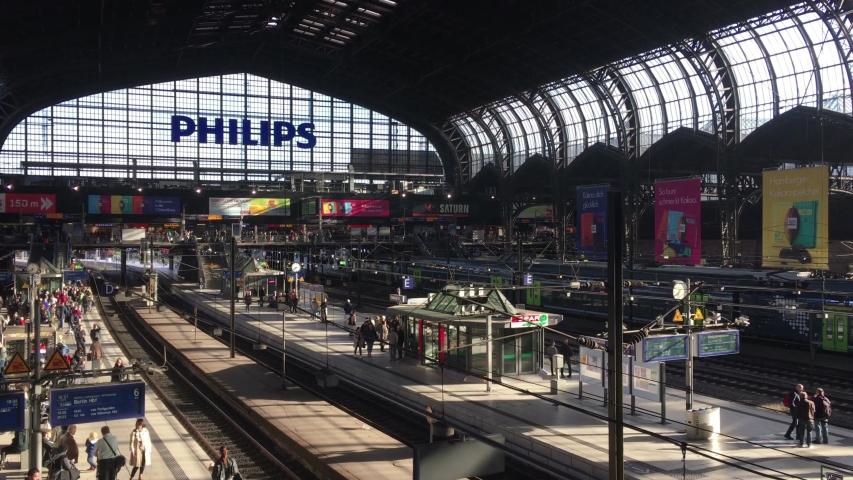 Hamburg, Germany - May 11, 2019: Wide Crane Shot of Hamburg Central Station Interior with travellers waiting for their train in sunshine / Establishing Shot