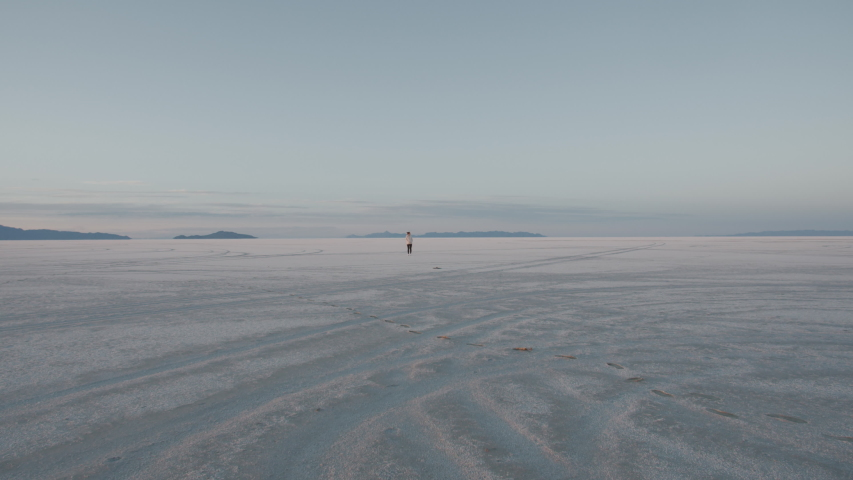 Young attractive female tourist walking on a surface of a Bonneville salt lake flats. 4K UHD 60 FPS SLOW MOTION
