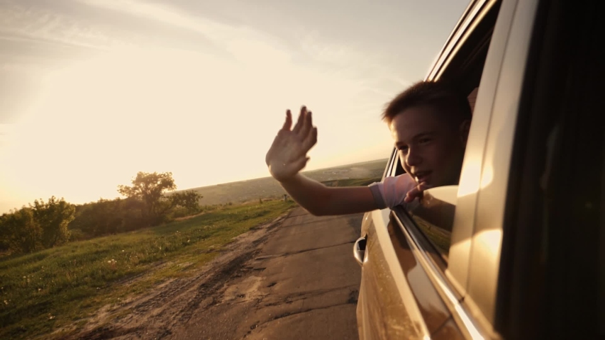 The boy looks out of the car window traveling the world. The boy's face in the sun with an arm stretched out of the car window. The concept of a happy family. Pursuit of travel and entertainment #1030057760