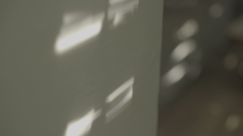 Sun and window createsing shadows on a wall in the morning light