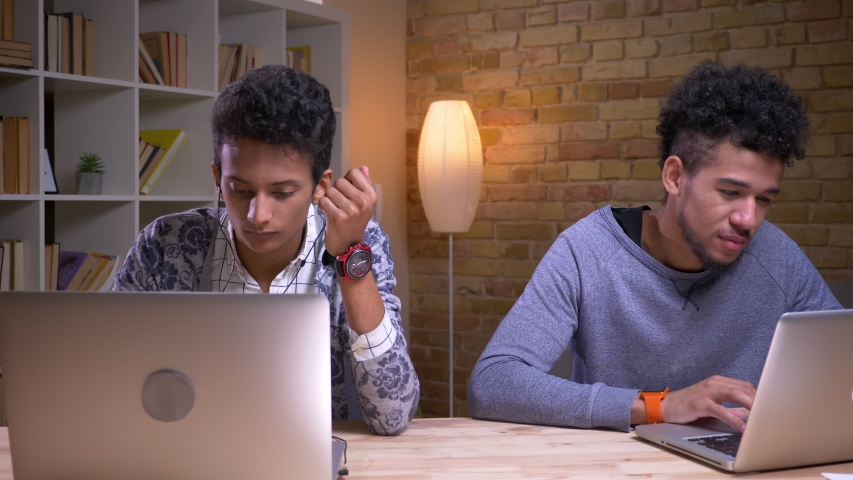 Closeup shoot of indian and african american male students using the laptops and studying online sitting indoors in the library together Royalty-Free Stock Footage #1030081403