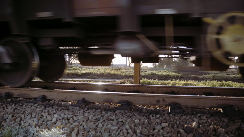 Close up of train wheels and wagons of an ore train pass by the camera.