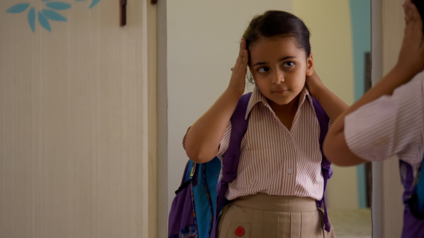 Cute little Indian child girl getting ready for school early morning - childhood. Stock footage of a sweet preschooler wearing school uniform and bag - looking in the mirror