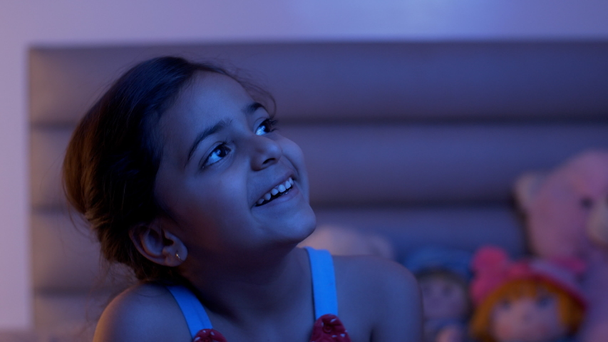 Pretty young Indian child girl watching stars from the window of her room at night. Stock video of a beautiful cute kid sitting in casual wear - looking outside from the window