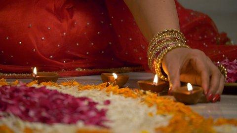 Diwali decoration - Indian women decorating her house with diyas and rangoli.