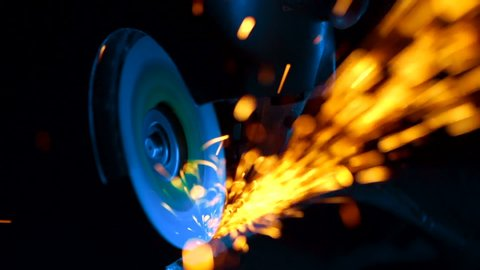 Close-up of worker at construction plant saws metal using circular saw. Industrial production, locksmith industry concept . Sparks from grinding wheel.