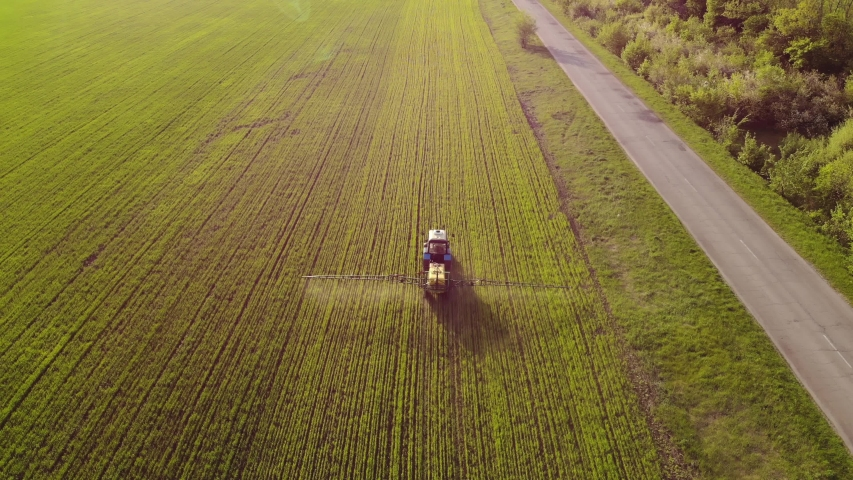 Aerial view of farming tractor spraying on field with sprayer, herbicides and pesticides at sunset. Farm machinery spraying insecticide to the green field, agricultural natural seasonal spring works.