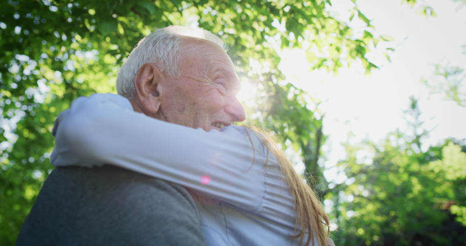 Slow motion of happy granddaughter is giving an effective hug to her grandfather as a sign of love and respect in a green park on a sunny day. | Shutterstock HD Video #1030112858