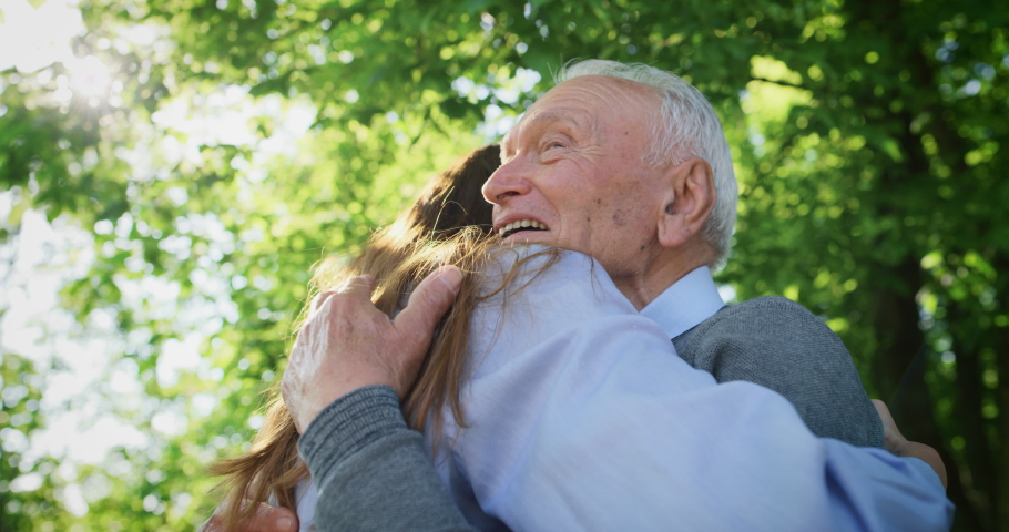Slow motion of happy granddaughter is giving an effective hug to her grandfather as a sign of love and respect in a green park on a sunny day.