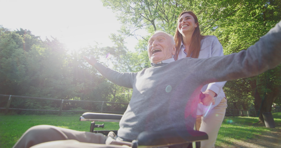 Slow motion of carefree and happy granddaughter and grandfather in a wheelchair having fun to run in a green park on a sunny day.