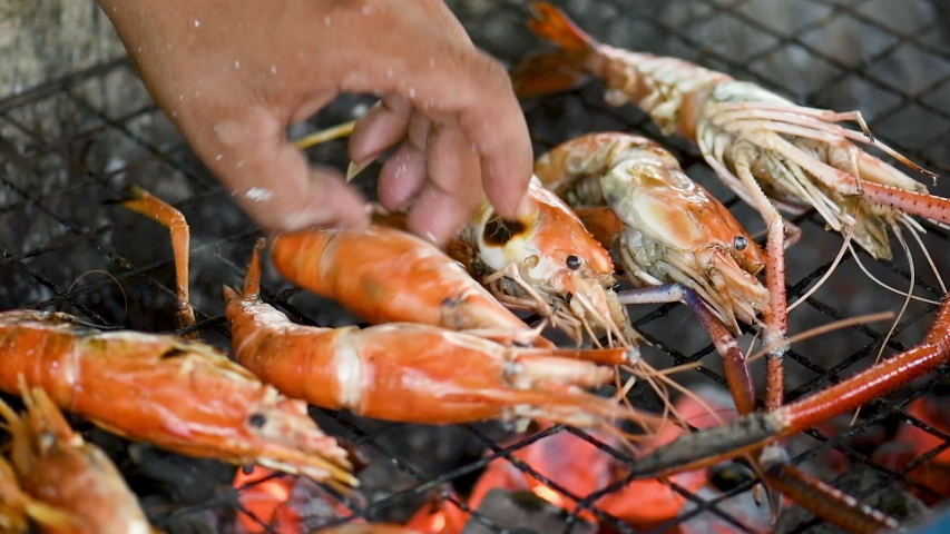 Delicious Grilled Prawns or Shrimps on Barbecue Grill. chef is cooking delicious prawn and burnt shrimp grill with flames on oven stove eat with seafood sauce,Fresh Asian Thai street sea food.     Shutterstock HD Video #1030117565