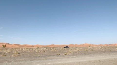 All-terrain 4x4 car circulates along the desert dunes in Morocco.