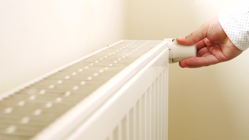 Person's Hand Adjusting Temperature On Thermostat To Control Heat In Central Home Heating System. Radiator near white wall. House in winter concept Royalty-Free Stock Footage #1030127237