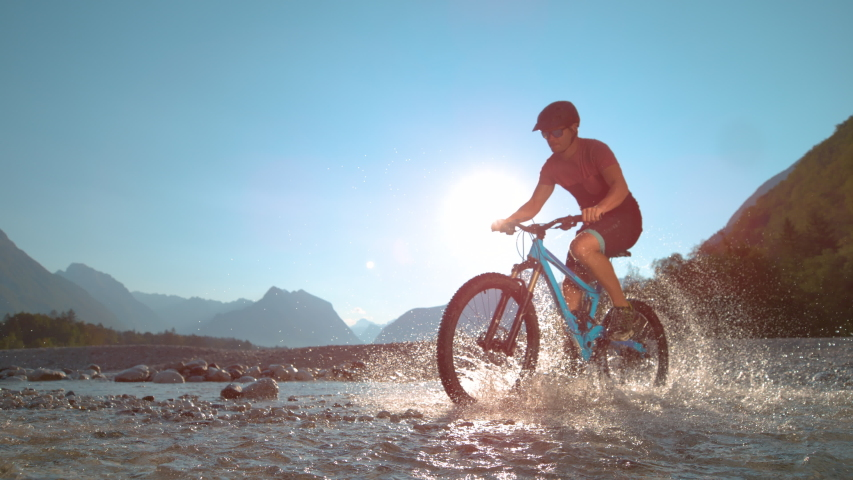 SUPER SLOW MOTION, LOW ANGLE: Fit man rides an e-bike in the shallow river and splashes water around him on a sunny summer day. Active male tourist rides a mountain bike in sunlit Soca river valley. | Shutterstock HD Video #1030129409