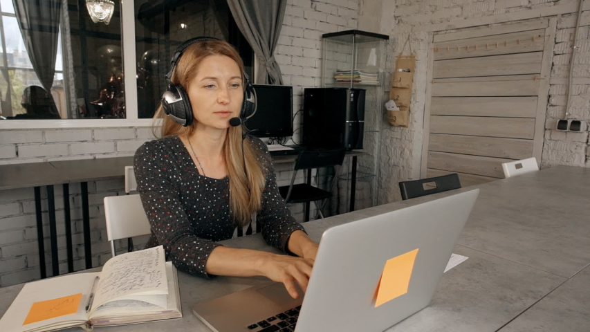 Mature, calm and confident smart woman using laptop and sitting behind desk table indoor coworking with light loft interior. Call center operator using headset and microphone in office | Shutterstock HD Video #1030131152