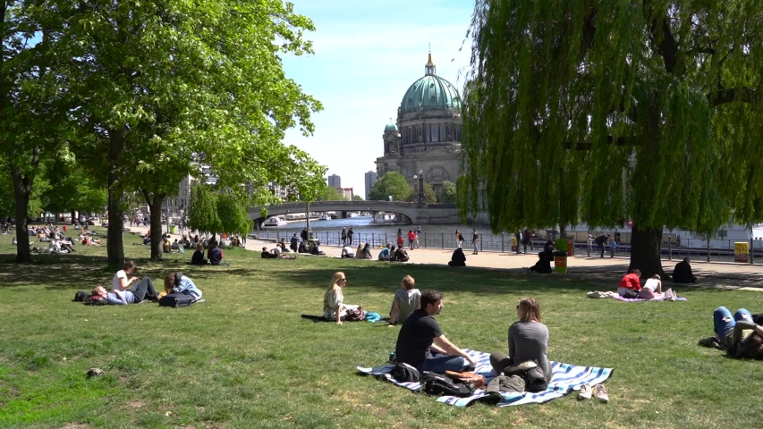 Berlin, Germany - May 12, 2019. People sunbathe on the lawn near the Berlin Cathedral and the Sprea river