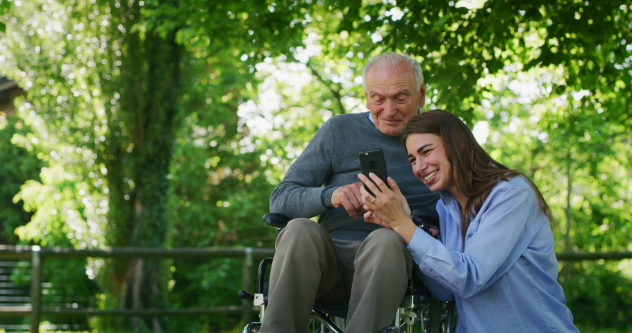 Slow motion of  happy granddaughter and grandfather in a wheelchair are having fun to look their photos or navigating in internet in cellular phone in a green park on a sunny day.