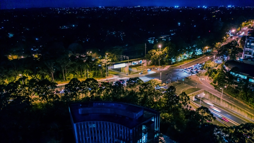 Aerial hyperlapse circling a busy city intersection with traffic and trains at night traffic - Pymble, Sydney, Australia