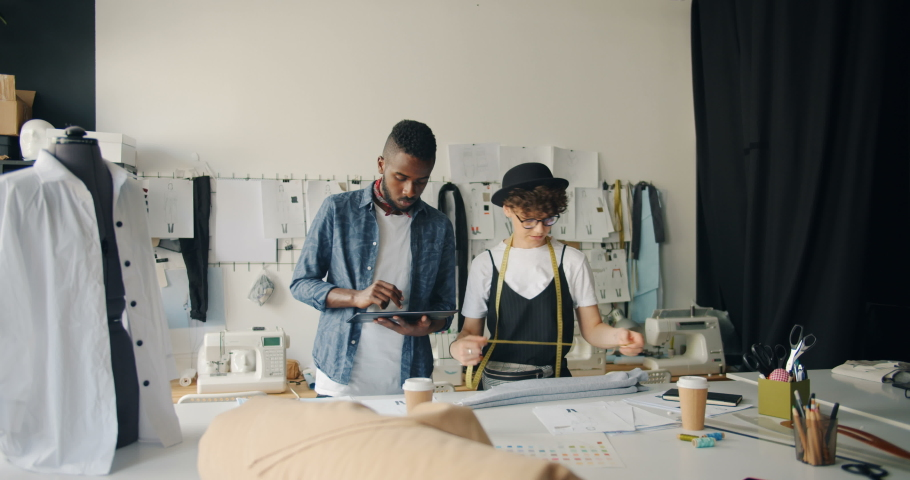 Creative dressmakers beautiful Caucasian girl and African American guy are designing clothing using tablet and measure-tape in studio. Technology and people concept. #1030159325