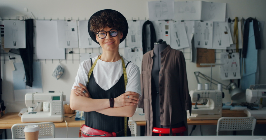 Portrait of happy young lady fashion designer smiling standing in workshop alone looking at camera. Small business owner and successful youth concept.