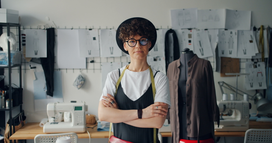 Portrait of independent young woman clothes designer standing in studio with arms crossed looking at camera. Successful youth and small business concept.