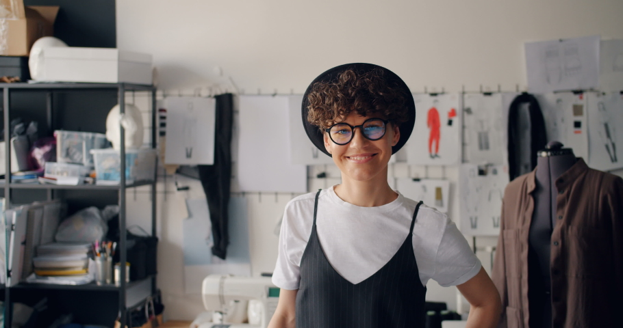 Portrait of pretty girl clothes designer smiling standing in modern workshop alone looking at camera. Beautiful successful people and workplace concept.