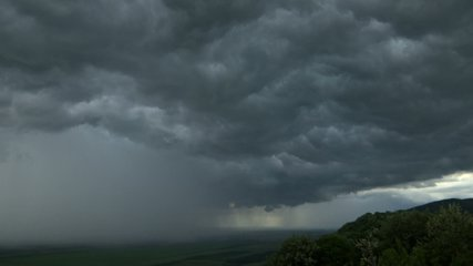 time lapse storm is coming - dramatic rain clouds approach the hill