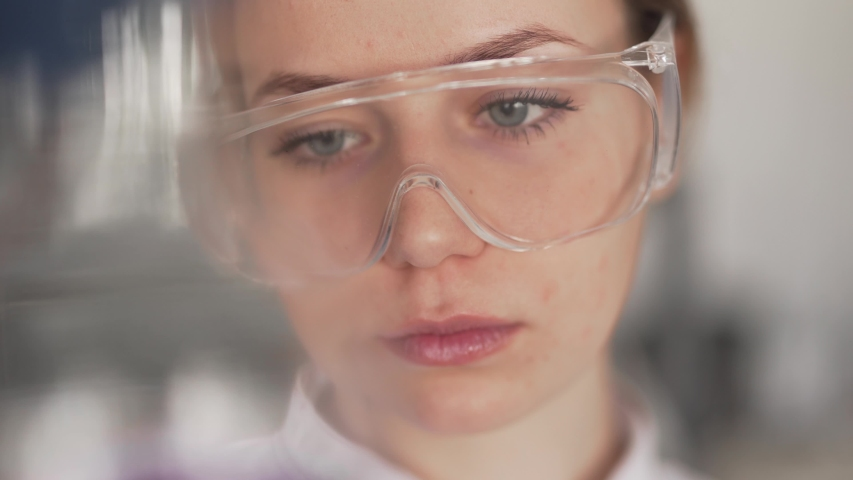 Potrait of Young Female Scientist in Modern Laboratory Looking at Liquid in Volumetric Flask Wearing Protective Glasses and Gloves. Light Camera Movement | Shutterstock HD Video #1030189859