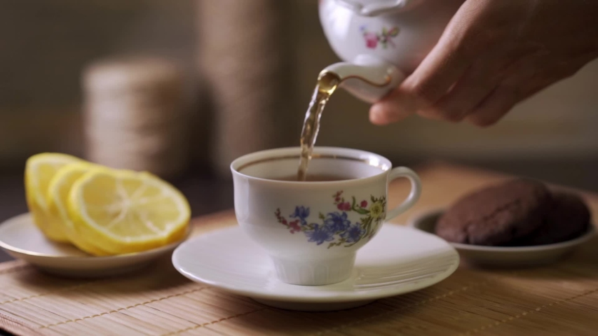 Tea being poured into tea cup. Dessert and hot drink. Lemon slices. Tea time.