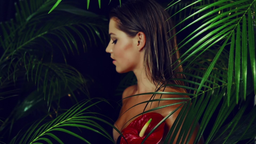 Beautiful girl with tanned skin holds  red exotic flower in her hands being among the tropical plants. Natural makeup and wet hair in girl amazon. Natural cosmetics, spa procedures. | Shutterstock HD Video #1030202027