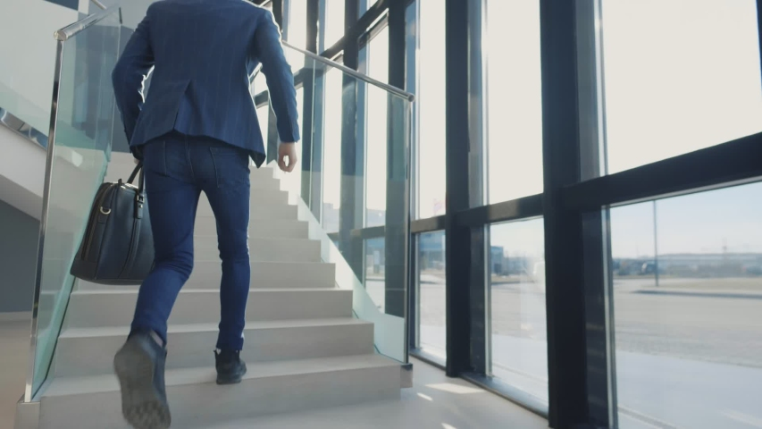 Office manager holding suitcase and running on office stairs