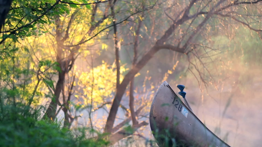 Canoes on shore on river bank and lake in the forest. Mist and fog in the air floating around with sun beams during golden hour. Sunlight shining through branches and trees. Pair of canoes by lake. | Shutterstock HD Video #1030210376