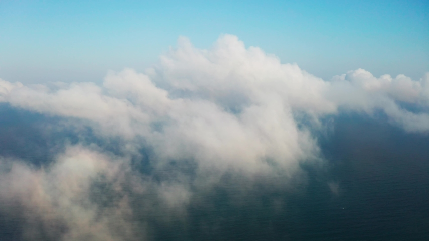 Moving white clouds blue sky on coastline and sea surface scenic aerial view. Drone flies forward high in blue sky through the fluffy clouds on panorama of the sea shore. The sun is hidden. Fog