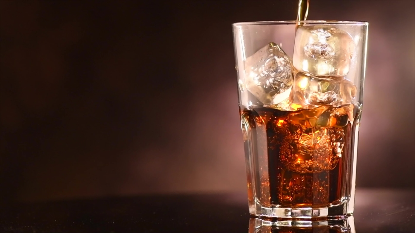 Pouring Cola with ice cubes close-up. Cola with Ice and bubbles in glass. Coke Soda closeup. Food background. Rotate glass of Cola fizzy drink over brown background. Slow motion 4K UHD video footage   Shutterstock HD Video #1030212500