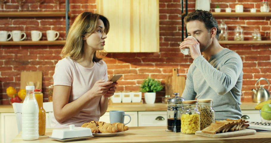 Young married couple having breakfast together in the kitchen in the morning, woman scrolling and tapping on the smartphone and showing something to the man on the screen while he sipping tea or | Shutterstock HD Video #1030214768
