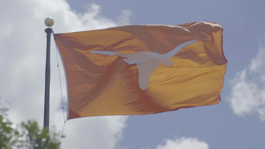 Austin, Texas - May 29 2019: A University of Texas longhorn flag flaps in the wind at 20% slow motion