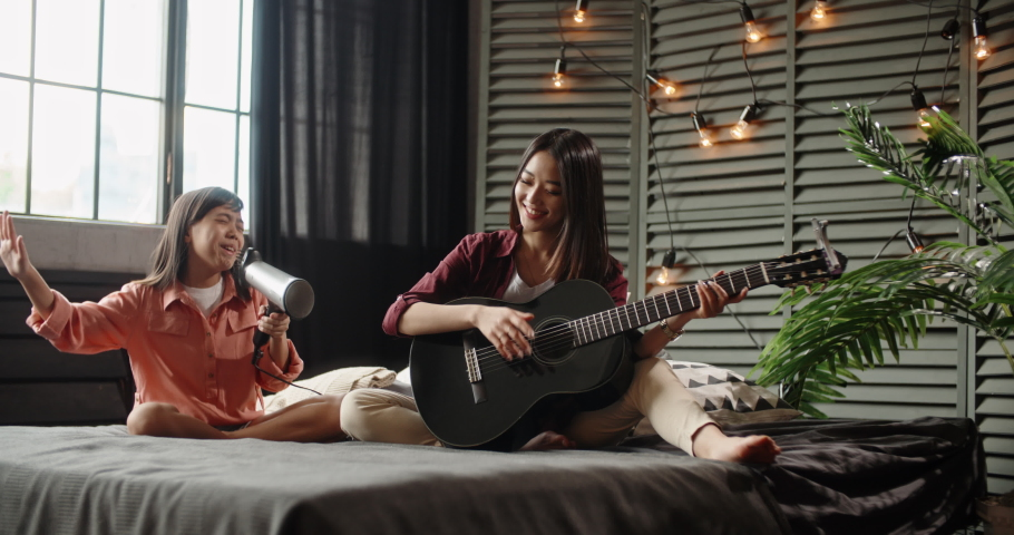 Two asian sisters sitting on bed, elder playing guitar while little kid is singing into hairdryer. Friends having fun spending time together at home - recreational pursuit, family time 4k