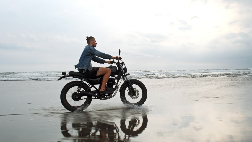 Man in riding motorcycle on beach. vintage motorbike on beach sunset on Bali. Young hipster male enjoying freedom and active lifestyle. Adventure travel concept. | Shutterstock HD Video #1030223432