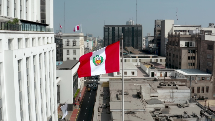 Peruvian flag waving against buildings in the historic center of Lima, the capital of Peru. Patriotism and nationalism concepts. Royalty-Free Stock Footage #1030227962