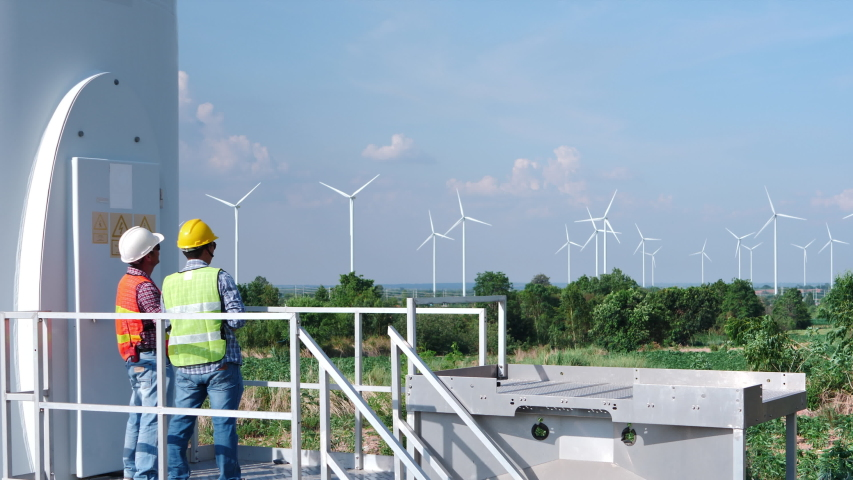 Two Asian engineers are checking the operation of wind turbines in wind farm field for production of electric power | Shutterstock HD Video #1030231559