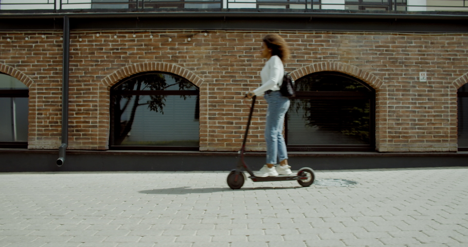 SIDE VIEW Attractive African American black female riding an electric city shared scooter in the street. 4K UHD  SLOW MOTION | Shutterstock HD Video #1030240046