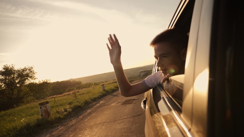 The boy looks out of the car window traveling the world. The boy's face in the sun with an arm stretched out of the car window. The concept of a happy family. Pursuit of travel and entertainment #1030262264